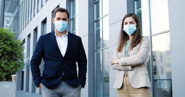 Portret młodego mężczyzny i kobiety rasy kaukaskiej w stylu biznesowym iw maskach medycznych, stojąc na odległość społeczną i patrząc na kamery. biznesmen i bizneswoman na zewnątrz podczas pandemii.
