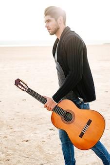 Portret młodego mężczyzny idącego przez morze z gitarą