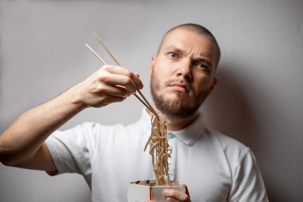 Portret młodego mężczyzny jedzenia makaronu