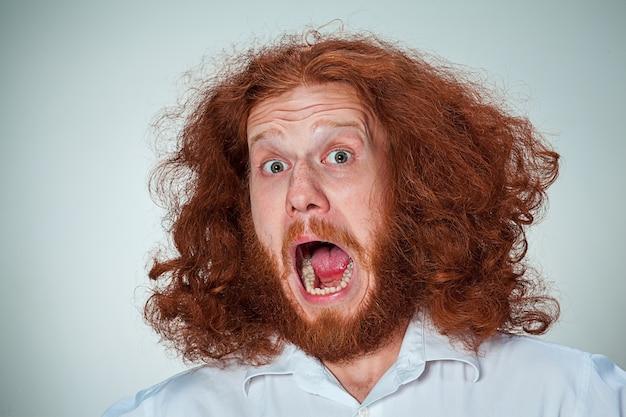 Portret młodego mężczyzny krzyczącego z długimi rudymi włosami iz zszokowanym wyrazem twarzy na szarym tle