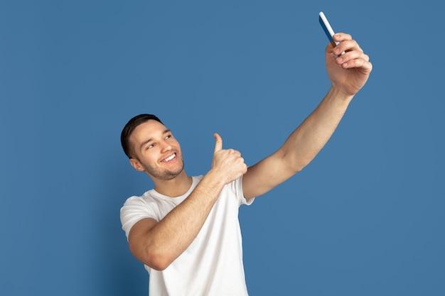 Portret młodego mężczyzny, który robi zdjęcie selfie na białym tle na niebieskiej ścianie studia