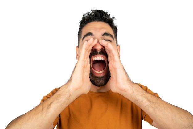 Portret młodego mężczyzny łacińskiej krzycząc i krzycząc na białym tle w studio.