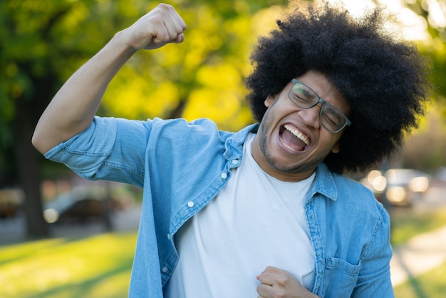 Portret młodego mężczyzny łacińskiej świętuje zwycięstwo na świeżym powietrzu. koncepcja miejska. koncepcja sukcesu.