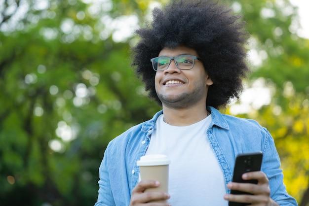 Portret młodego mężczyzny łacińskiej za pomocą swojego telefonu komórkowego, stojąc na zewnątrz na ulicy. koncepcja miejska.