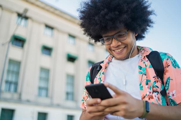 Portret młodego mężczyzny łacińskiej za pomocą swojego telefonu komórkowego, stojąc na zewnątrz na ulicy