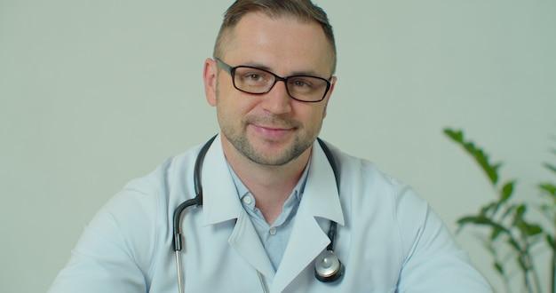 Portret młodego mężczyzny lekarza w okularach w szpitalu, patrząc na kamery.