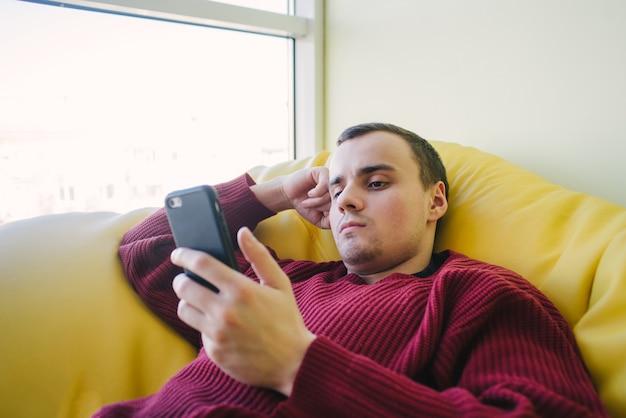 Portret młodego mężczyzny leżącego w fotelu worek jasny żółty i użyj telefonu komórkowego. rekreacja pasywna. portret w pomieszczeniu