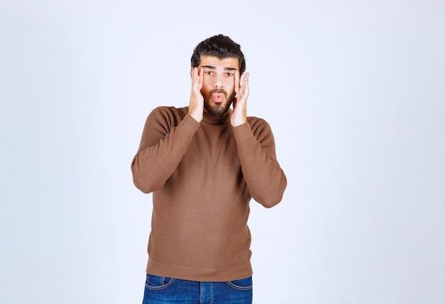 Portret młodego mężczyzny model stojący i uważnie obserwujący. zdjęcie wysokiej jakości