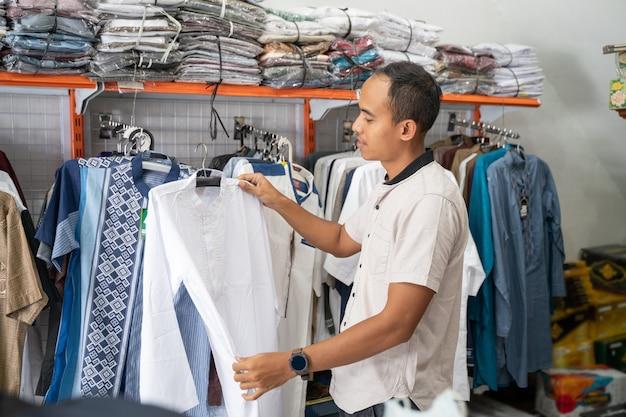 Portret młodego mężczyzny muzułmańskiego azjatyckiego zakupy na ubrania w sklepie