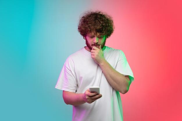 Portret młodego mężczyzny na gradientowym tle studyjnym w neonowym