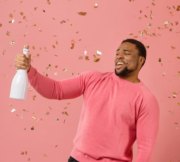 Portret młodego mężczyzny na imprezie z butelką szampana