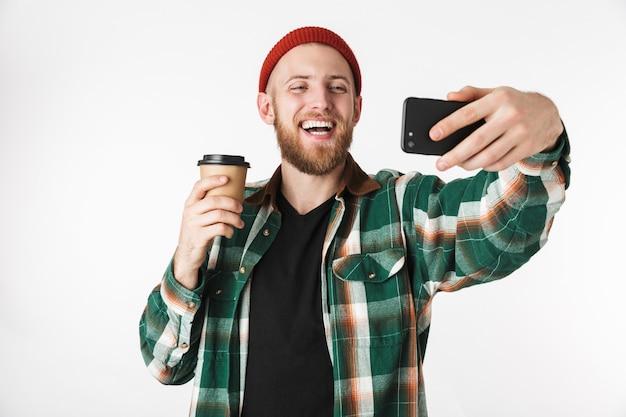 Portret młodego mężczyzny na sobie koszulę w kratę, trzymając papierowy kubek z kawą i przy użyciu telefonu komórkowego, stojąc na białym tle nad białym tle