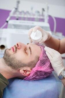 Portret młodego mężczyzny na zabieg czyszczenia twarzy przez kobietę kosmetologa w klinice urody. kosmetyczka ociera twarz pacjenta wacikami. koncepcja branży kosmetycznej. facet leży na kanapie.