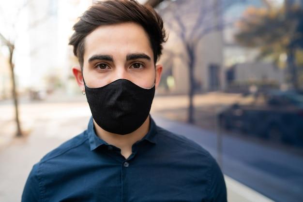Portret młodego mężczyzny noszącego maskę ochronną, stojąc na zewnątrz na ulicy