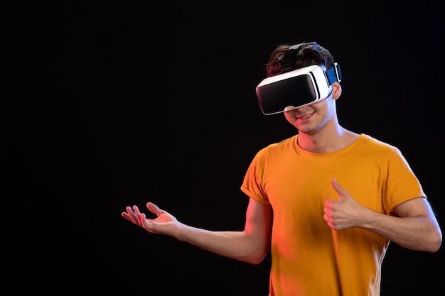 Portret młodego mężczyzny noszącego zestaw słuchawkowy wirtualnej rzeczywistości ciemny gry wideo d
