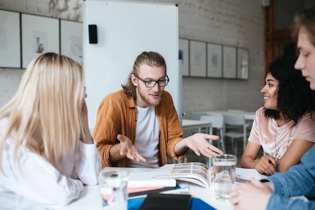 Portret młodego mężczyzny o blond włosach i brodzie, emocjonalnie wyjaśnia coś swoim znajomym. grupa ludzi siedzących przy stole i pracujących razem