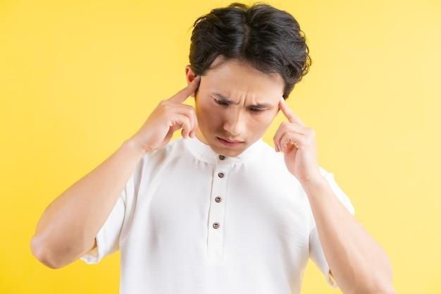 Portret młodego mężczyzny o bólu głowy na żółto