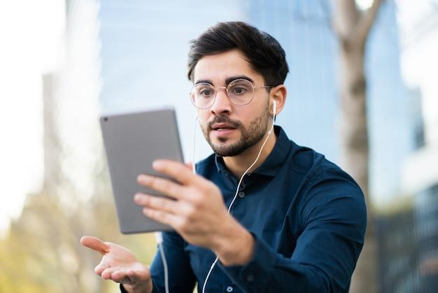 Portret młodego mężczyzny o rozmowie wideo na cyfrowym tablecie, stojąc na ławce na zewnątrz