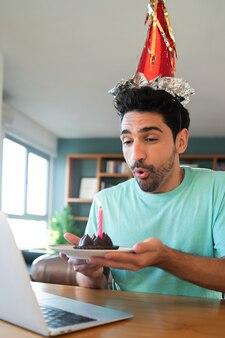 Portret młodego mężczyzny obchodzi urodziny na rozmowie wideo z domu z laptopem i ciastem. nowa koncepcja normalnego stylu życia.