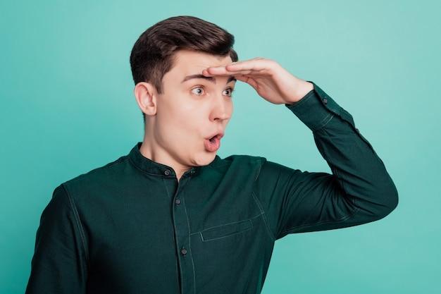 Portret młodego mężczyzny odwracającego wzrok z głową ręki na turkusowym tle
