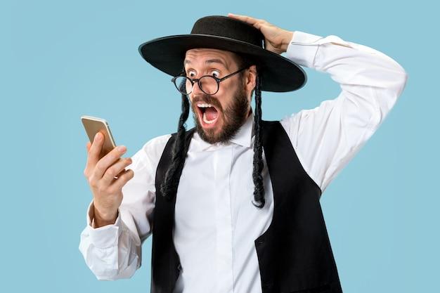 Portret młodego mężczyzny ortodoksyjnego żyda z telefonem komórkowym o godz