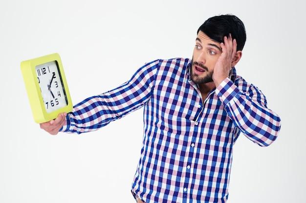 Portret młodego mężczyzny, patrząc na zegar ścienny na białym tle na białej ścianie