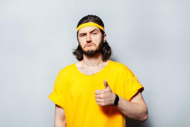 Portret młodego mężczyzny pewnie w żółtej koszuli pokazując kciuk do góry.