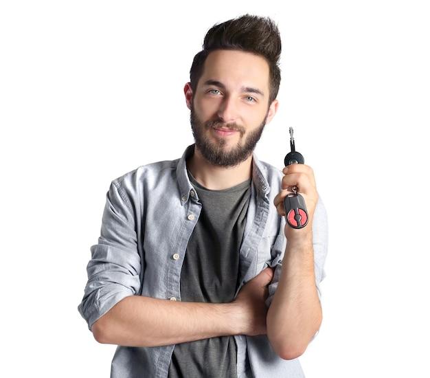 Portret młodego mężczyzny posiadającego kluczyk do samochodu, na szaro
