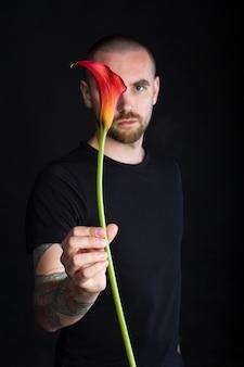 Portret młodego mężczyzny posiadającego pojedynczy czerwony kwiat calla na białym tle