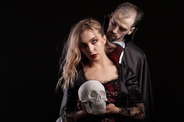 Portret młodego mężczyzny przebranego za drakulę, patrzącego na szyję swojej wampirzej kobiety. przystojny mężczyzna i mizerny mężczyzna przebrany za halloween.