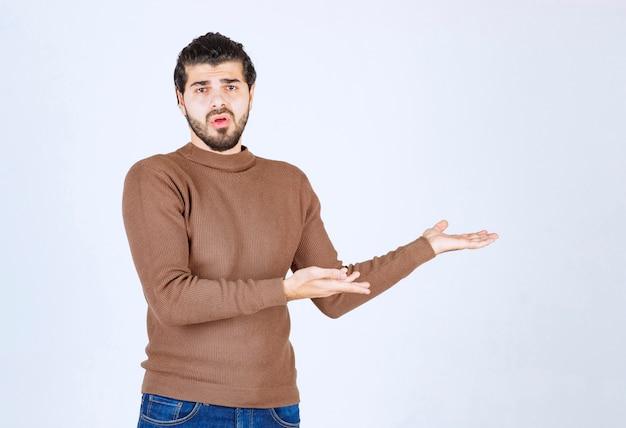 Portret młodego mężczyzny przedstawiający lub pokazujący miejsce na kopię na jego dłoni.
