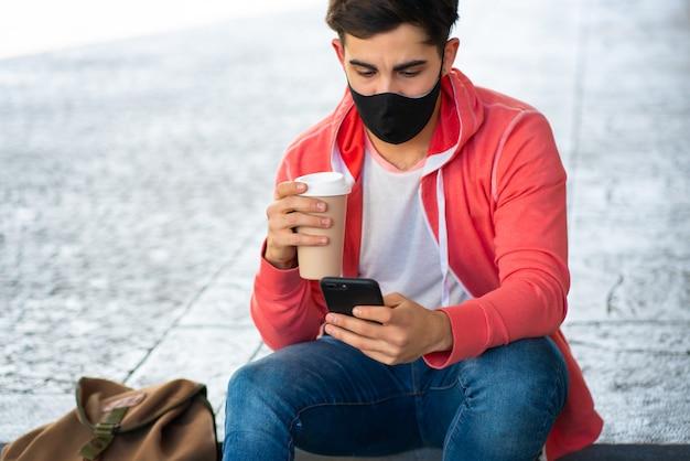 Portret młodego mężczyzny przy użyciu swojego telefonu komórkowego i picia kawy siedząc na zewnątrz na ulicy. mężczyzna nosi maskę na twarz. koncepcja miejska.