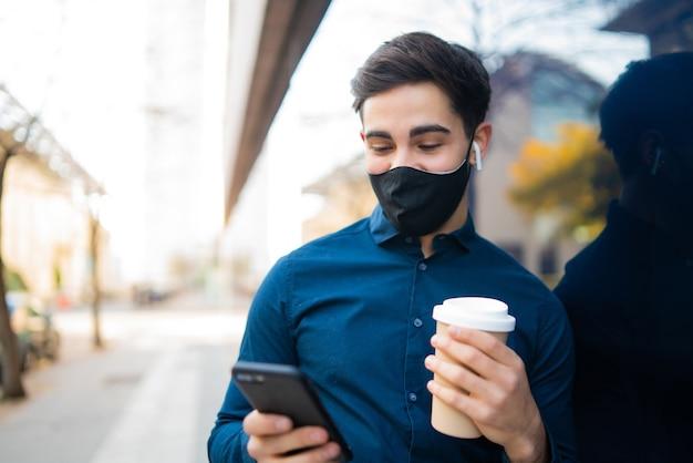 Portret młodego mężczyzny przy użyciu swojego telefonu komórkowego i trzymając filiżankę kawy, stojąc na zewnątrz na ulicy. nowa koncepcja normalnego stylu życia. koncepcja miejska.