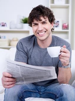 Portret młodego mężczyzny przystojny z filiżanką kawy, czytanie gazety