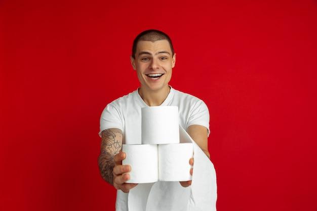 Portret młodego mężczyzny rasy kaukaskiej na czerwonym studio