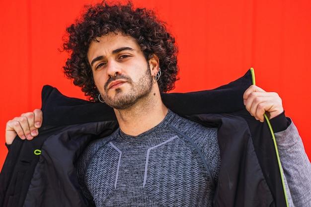 Portret młodego mężczyzny rasy kaukaskiej na czerwonym