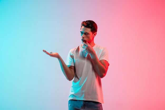 Portret młodego mężczyzny rasy kaukaskiej na gradientowym tle bluepink studio w świetle neonowym