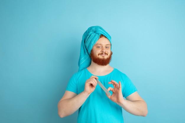 Portret młodego mężczyzny rasy kaukaskiej w jego rutynowej pielęgnacji skóry i urody.