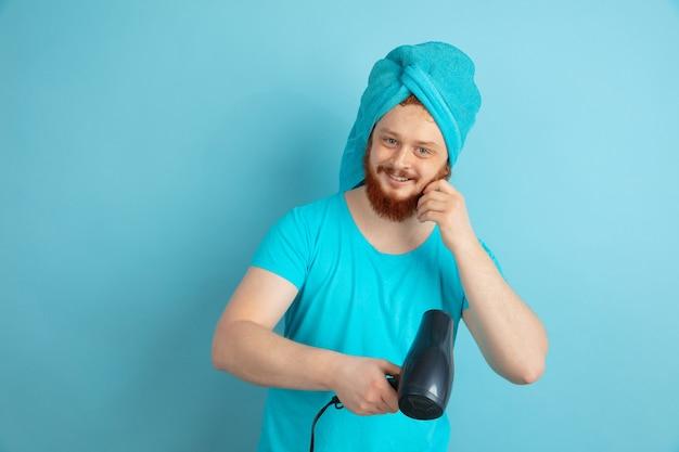 Portret młodego mężczyzny rasy kaukaskiej w jego rutynowej pielęgnacji skóry i urody