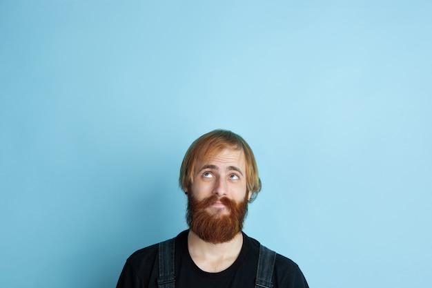 Portret młodego mężczyzny rasy kaukaskiej wygląda marzycielsko, słodko i szczęśliwie
