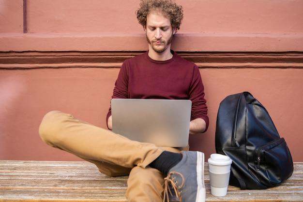 Portret młodego mężczyzny rasy kaukaskiej za pomocą swojego laptopa siedząc na zewnątrz. koncepcja technologii.