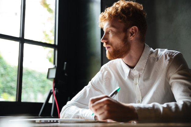 Portret młodego mężczyzny redhead pisania w zeszycie