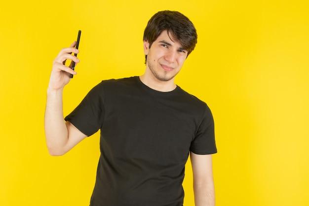 Portret młodego mężczyzny rozmawia przez telefon komórkowy z żółtym.