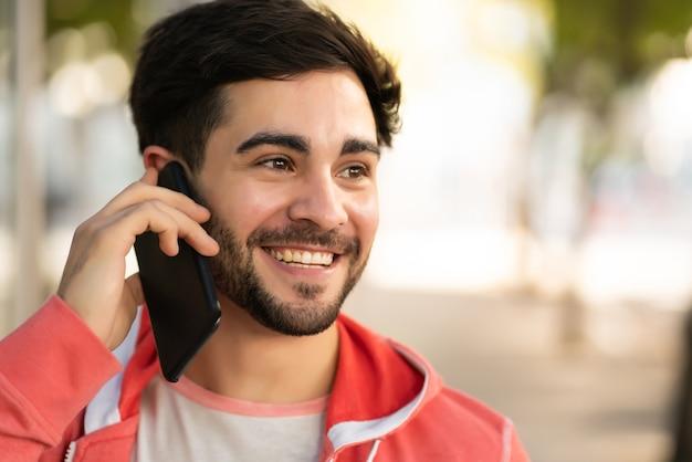 Portret młodego mężczyzny rozmawia przez telefon, stojąc na zewnątrz na ulicy. koncepcja miejska.