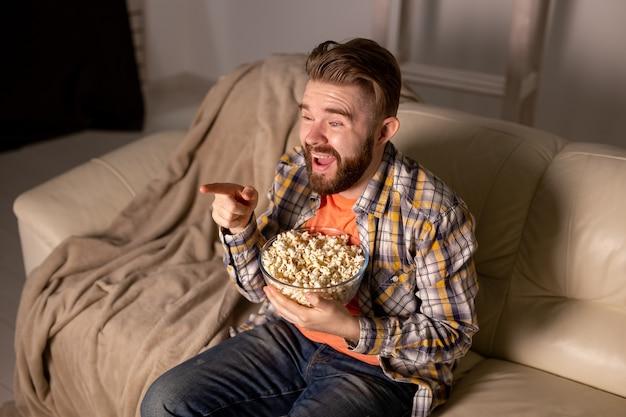 Portret młodego mężczyzny siedzącego na kanapie i oglądającego telewizję i jedzącego popcorn