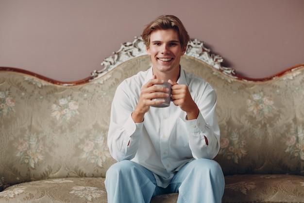 Portret młodego mężczyzny siedzącego, pijącego i cieszącego się popołudniową herbatą lub kawą