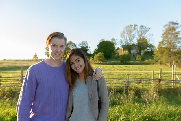 Portret młodego mężczyzny skandynawskiego i młodej kobiety azjatyckiej jako wieloetniczna para razem w przyrodzie na zewnątrz