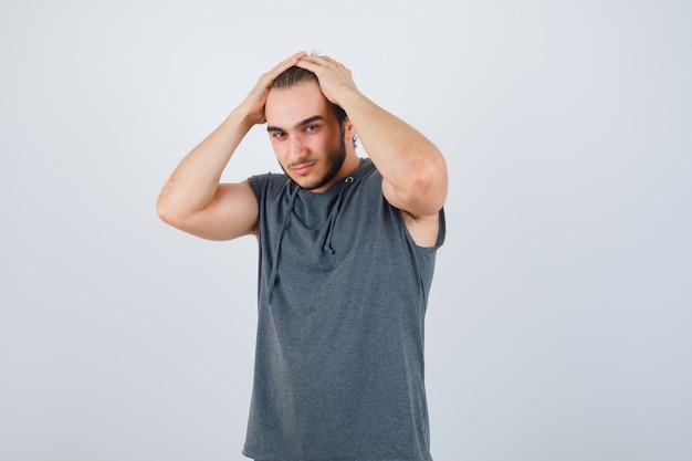 Portret młodego mężczyzny sprawnego trzymającego ręce na głowie w bluzie bez rękawów i wyglądającego atrakcyjnie z przodu
