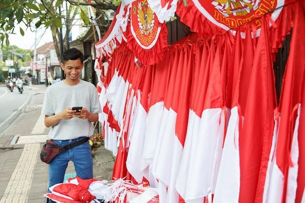 Portret młodego mężczyzny sprzedającego indonezyjską flagę narodową