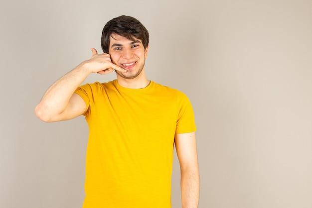 Portret młodego mężczyzny stojącego i czyniąc znak wywoławczy przeciwko szarości.